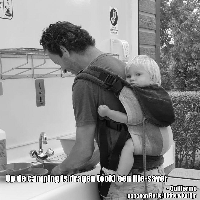 papa draagt peuter met wompat op de caming afwassend met de tekst: Op de camping is dragen (ook) een lifesaver