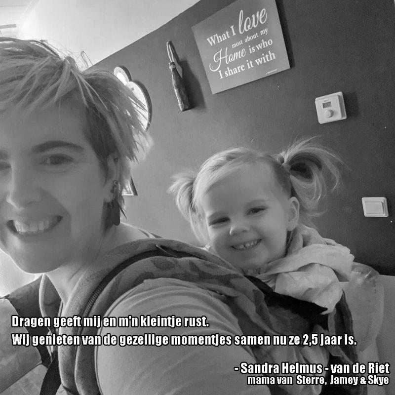 Blije peuter bij moeder op de rug in tula draagzak tekst: Dragen geeft mij en m'n kleintje rust. Wij genieten van de gezellige momentjes samen nu ze 2,5 jaar is.