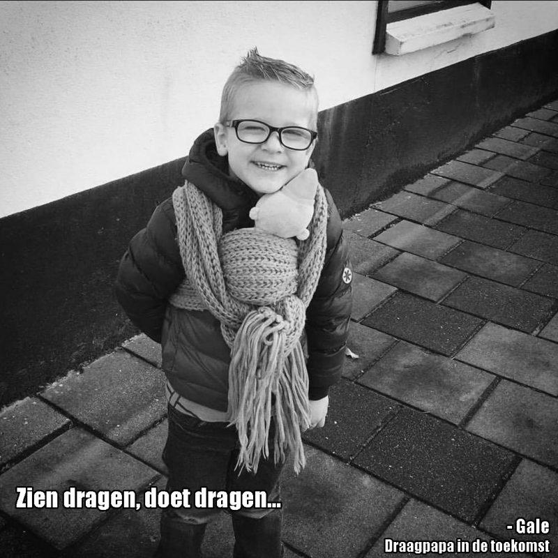 Peuter jongen draag heel trotst knuffel in draagdoek met de tekst: Zien dragen doet dragen